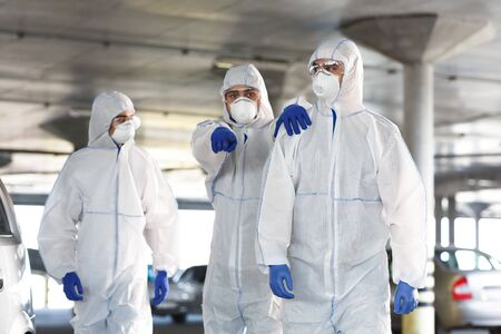 Frightened Man in virus protective suit showing with finger on something, coronavirus pandemic, biohazard, covid 19