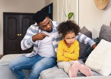 African american father scolds little daughter. Girl offended and turned away