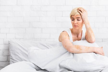 Depressed middle aged woman sitting on bed at home and feeling upset, copy space