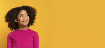 Cute Little African Girl Looking Aside At Copy Space Over Yellow Background, Panorama