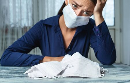 Stop Panic Concept. Depressed woman wearing face mask sitting with bunch of medical masks on the desk