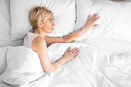 Loneliness. Sad middle aged woman lying in double bed reaching for her husband and touching empty pillow, copy space