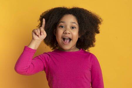 I Have Idea. Little african american girl pointing finger up and looking at camera, standing over yellow studio background with free space