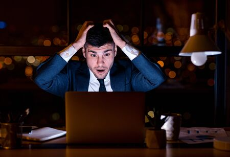 Bad Business News. Shocked Businessman Cupping Head In Hands Looking At Laptop Sitting In Modern Office At Night.