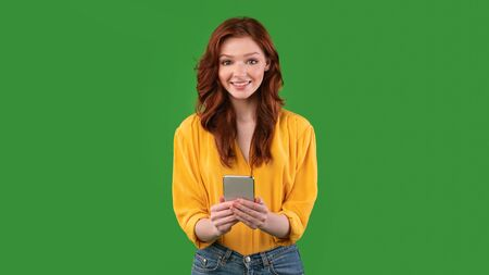 Mobile App. Happy Red-Haired Girl Using Smartphone Application Standing On Green Background. Studio Shot, Panorama