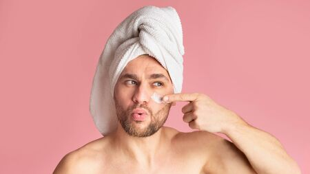 Skin care products for men. Cute guy with towel on his head smears his face with cream, free space Archivio Fotografico