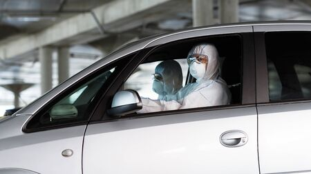 Medical workers in coronavirus suits driving a car and looking for sick people to help them, panorama, copy space