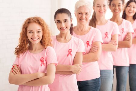 Multiethnic Ladies Volunteers In Pink Cancer Awareness T-Shirts Standing Together In Line Posing Crossing Hands On White Background. Shallow Depth Banque d'images