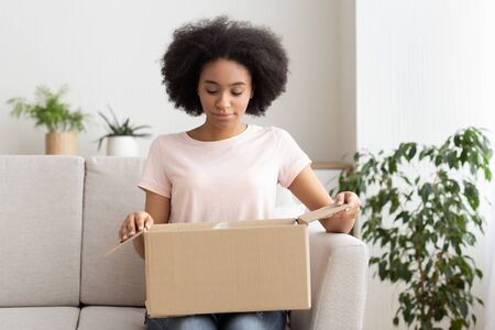 Millennial african american female opens postal package buyed on online store
