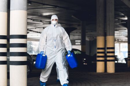 Worker in protective suit making wet disinfection of streets for prevention coronavirus epidemic, copy space