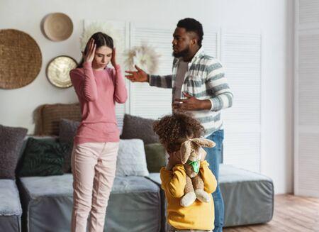 Divorce concept. International parents quarrel, daughter cries closing with toy
