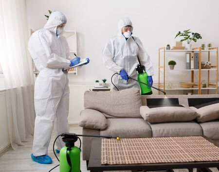 Workers wearing virus protective suits disinfecting home surfaces with spray chemicals to prevent the spreading of the coronavirus