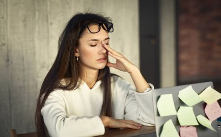 Lack of sleep due to work concept. Millennial woman rubbing her eyes Stock Photo