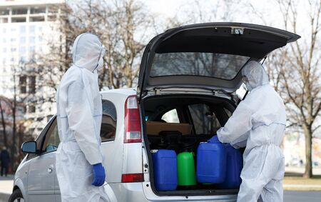 Family in virus protective suits buying disinfectants and packing them into car
