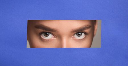 Conceptual Photo. Curious attractive girl peeping out of torn blue paper, empty space