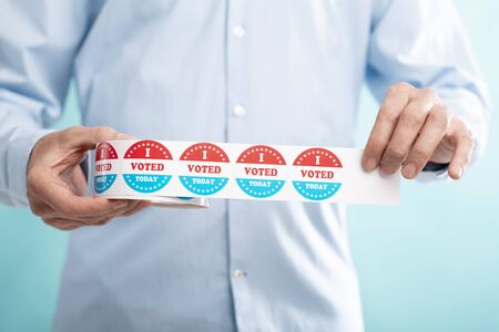 USA elections concept. Man holding stickers roll with text i voted today on blue background