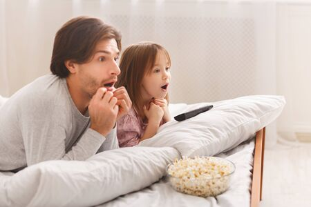 Shocked Dad And His Little Girl Watching Horror, laying on bed and eating popcorn, copy space Stock Photo