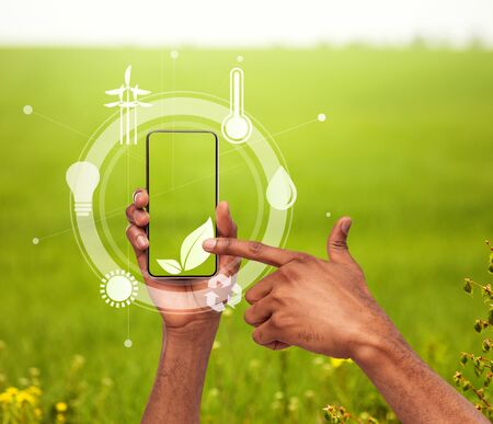 Green living technologies. Creative collage with man pointing at plant symbol among ecological icons on mobile phone