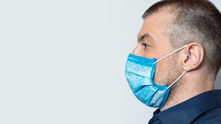 Coronavirus. Man Wearing Protective Medical Mask Posing Over White Studio Background. Side View, Copy Space Stock Photo