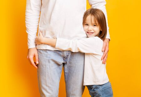 I love you dad. Close up of cute smiling little girl hugging her dad over yellow background Banco de Imagens