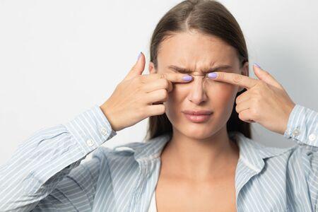 Coronavirus Hygiene Concept. Woman Touching Eyes Standing Over White Background. Studio Shot 版權商用圖片