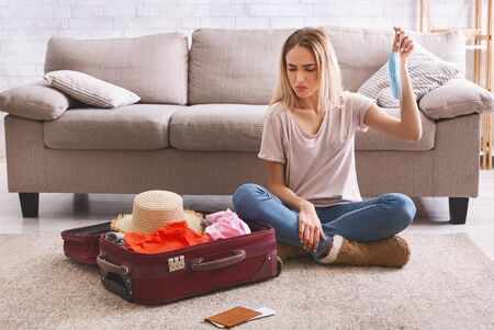 Woman with mask in hand looks sadly at suitcase with clothes Foto de archivo