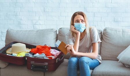 Cancellation of flights during the coronavirus. Sorrowful woman stayed at home alone
