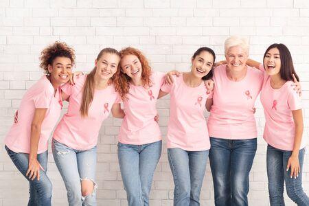 Grupa Wsparcia Raka Piersi. Różnorodne Kobiety I Dziewczęta W Różowe Koszulki Z Symbolem Raka Przytulanie Stojących Na Białym Tle.