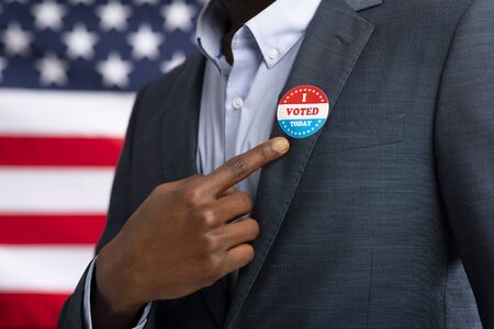 Patriotic elections in America 2020. African American US resident showing with finger on inscription I voted today