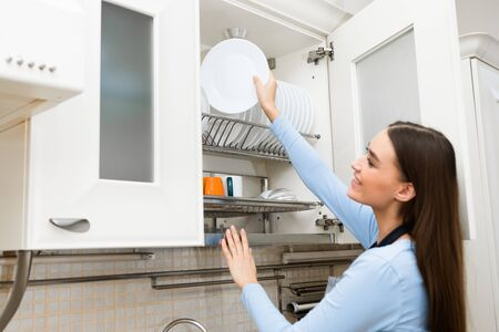 Housework Concept. Smiling woman putting or taking clean plate on the shelf in kitchen cupboard