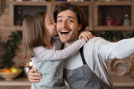 I Love You, Daddy. Little Girl Cuddling And Kissing Father While They Taking Selfie In Kitchen, Having Fun At Home Together, Closeup