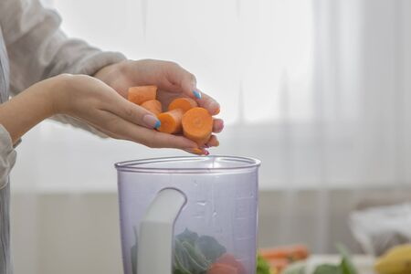 Woman blending carrot and other vegetables to make a healthy smoothie at home, copy space