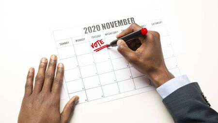 African man writing vote text in Calendar, US General Election Day Circled November 3th 2020, panorama