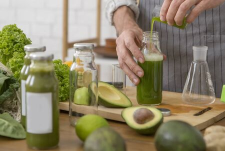 Man vegetarian adding green extract to detox smoothie, diet concept, home healthy food