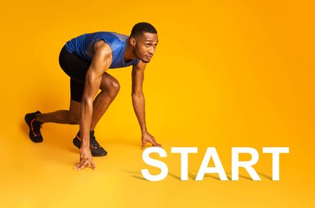 Time To Start. Muscular black sportsman preparing for a run, looking up at copyspace, panorama, yellow studio wall