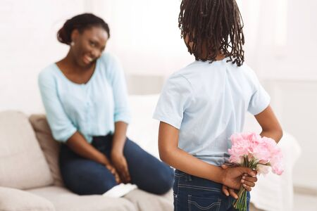 Making Surprise At Home. Unrecognizable African Child Hiding Flowers For Mum Behind Back. Selective Focus.
