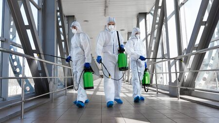 Biological hazard. Epidemic of the coronavirus. Men in a protective suit and mask disinfecting tunnel with gas.