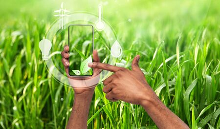 Collage with young man choosing plant symbol among eco icons on smartphone in field, copy space. Panorama