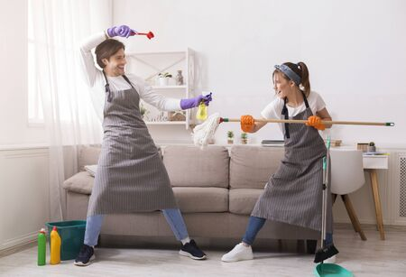 Cleaning Fun. Joyful Young Couple Fooling While Tidying Up Their Flat, Playfully Fighting With Brush And Mop, Staying At Home, Free Space