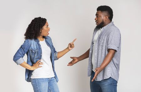 Misunderstanding in relationship. Furious black woman blaming her boyfriend, standing together over light background with free space