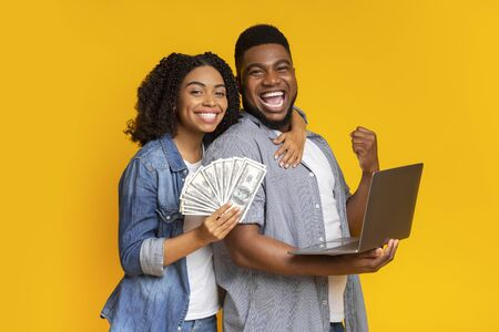Sport betting online concept. Excited african couple with bunch of dollars and laptop in hands celebrating win together, yellow background Banque d'images