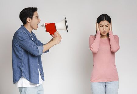 Misunderstanding in couple. Angry asian guy shouting through megaphone at his annoyed girlfriend, grey background
