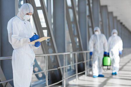 Virologists in protective hazmat suits controlling epidemic, pathogen respiratory quarantine coronavirus concept, copy space