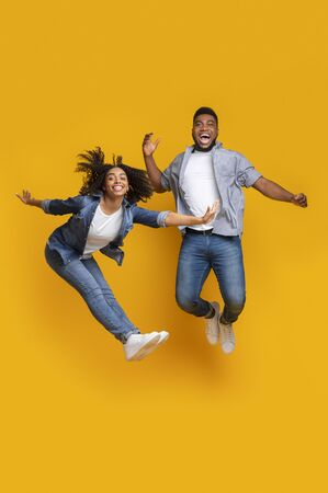 Happy African Couple Fooling Together, Jumping High In Air Over Yellow Studio Background And Looking At Camera, Copy Space 免版税图像