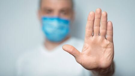 Stop Coronavirus. Unrecognizable Man In Medical Mask Gesturing Stop Standing Over Gray Background In Studio. Panorama, Selective Focus Stock Photo
