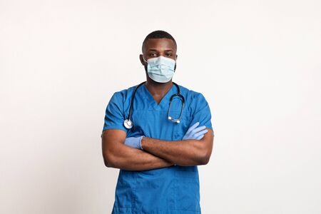 Confident black doctor in face mask and gloves over white studio background, copy space
