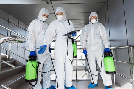 Virologists making professional cleaning with disinfectant spray or gas, outdoor surfaces, quarantine, coronavirus epidemic