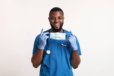 Use face mask during quarantine. Positive african male doc wearing face mask over white background