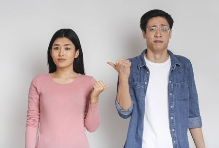 Asian couple pointing at each other with facial expression of disgust, grey studio background Standard-Bild