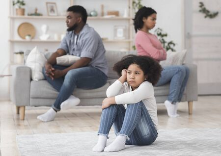 Family Quarrels Concept. Upset little black girl sitting on floor separately from parents after their argue, selective focus on kid